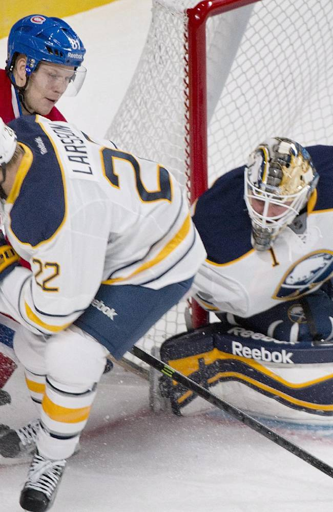 Montreal Canadiens' Lars Eller, left, moves in on Buffalo Sabres' goaltender Jhonas Enroth, right, as Sabres Johan Larsson defends during the first period of an NHL pre-season hockey game, Sunday, Sept. 15, 2013 in Montreal