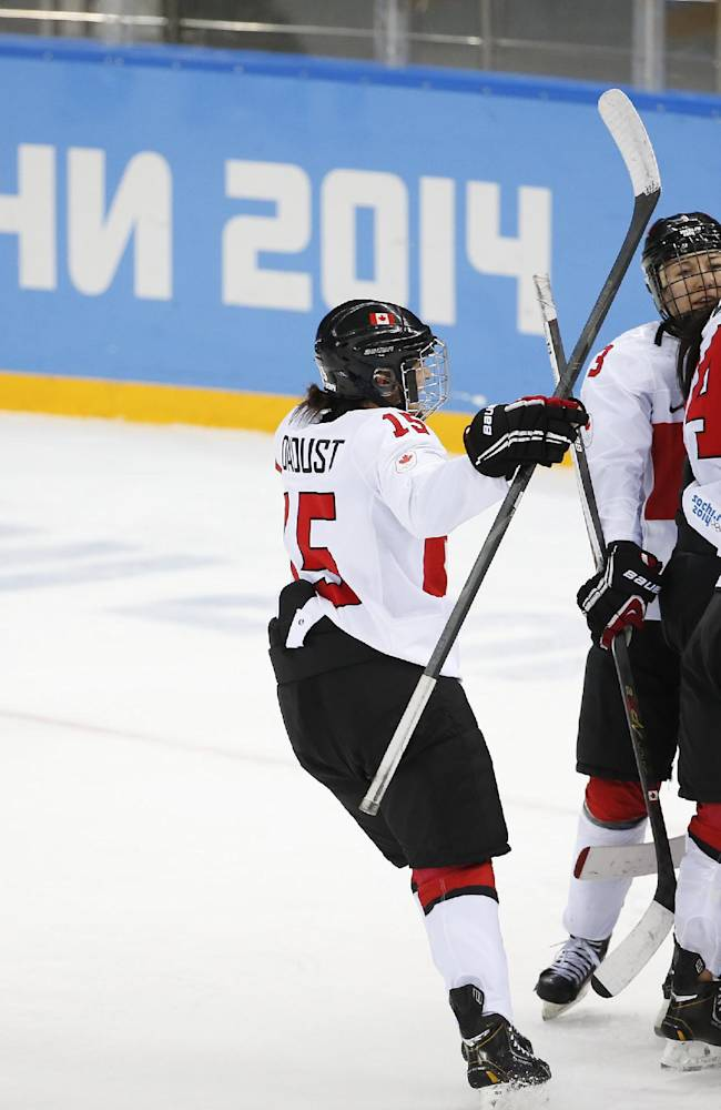 Team Canada celebrates as Alina Muller of Switzerland skates off the ice after Canada beat Switzerland 3-1 in a  2014 Winter Olympics women's semifinal ice hockey game at Shayba Arena, Monday, Feb. 17, 2014, in Sochi, Russia