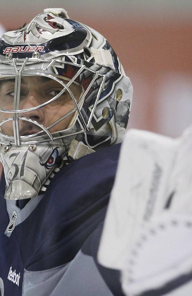 Winnipeg Jets' goaltender Ondrej Pavelec (31) from the Czech Republic keeps his eye on the puck as he makes the save at NHL hockey training camp Thursday, Sept. 12, 2013, in Winnipeg, Manitoba
