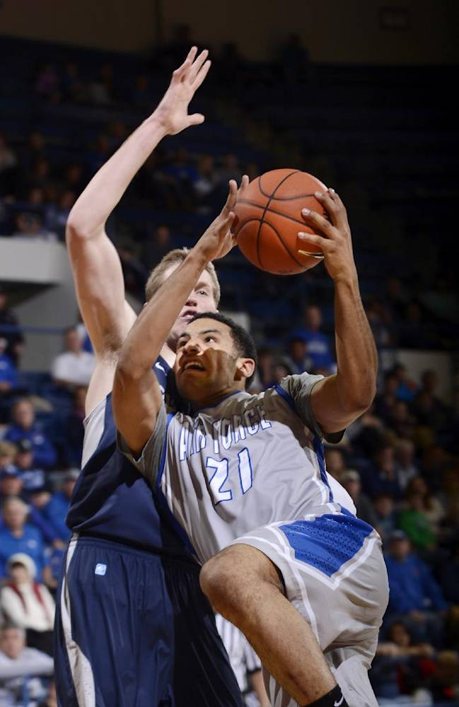 Air Force Academy forward DeLovell Earls, right, drives past Utah State's Kyle Davis in the second half of an NCAA college basketball game Wednesday, Jan. 1, 2014, in Air Force Academy, Colo