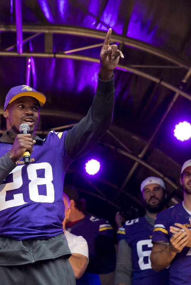 Minnesota Vikings running back Adrian Peterson, left, speaks on stage flanked by his teammates, from left, center John Sullivan, injured quarterback Christian Ponder and defensive tackle Kevin Williams during an American football NFL fan rally event in Regent Street, central London, Saturday, Sept. 28, 2013.  The Minnesota Vikings are to play the Pittsburgh Steelers at Wembley stadium in London on Sunday, Sept. 29 in a regular season NFL game