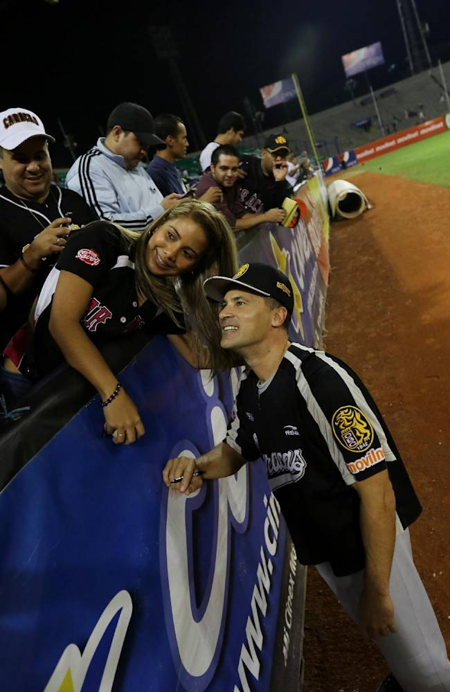 In this Nov. 27, 2013 photo, Omar Vizquel, one of Venezuela's best contributions to the big leagues, poses for a photo with fans prior a baseball game between Leones of Caracas and Magallanes of Valencia in Caracas, Venezuela. The former Cleveland Indians shortstop helped manage the Leones this season to prepare for his debut as an infield coach with the Detroit Tigers