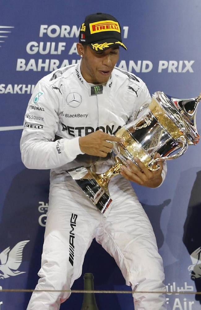 Mercedes driver Lewis Hamilton of Britain holds his trophy after winning the Bahrain Formula One Grand Prix at the Formula One Bahrain International Circuit in Sakhir, Bahrain, Sunday, April 6, 2014