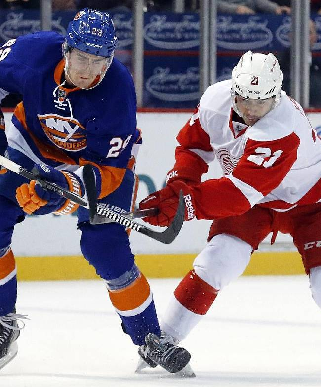 New York Islanders center Brock Nelson (29) and Detroit Red Wings left wing Tomas Tatar (21), of the Czech Republic, battle for the puck in the first period of an NHL hockey game, Monday, Dec. 23, 2013, in Detroit
