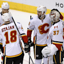 Calgary Flames goalieJoni Ortio (37), of Finland, celebrates the Flames' 4-1 win over the Arizona Coyotes with teammates Matt Stajan (18), Dennis Wideman (6) and Brandon Bollig after an NHL hockey game Thursday, Jan. 15, 2015, in Glendale, Ariz The Associ