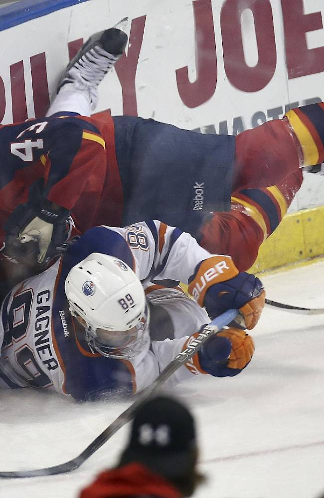 Florida Panthers' Mike Weaver (43) and Edmonton Oilers' Sam Gagner (89) slide into the wall, while chasing the puck, during the second period of an NHL hockey game in Sunrise, Fla., Tuesday, Nov. 5, 2013. (AP J Pat Carter)