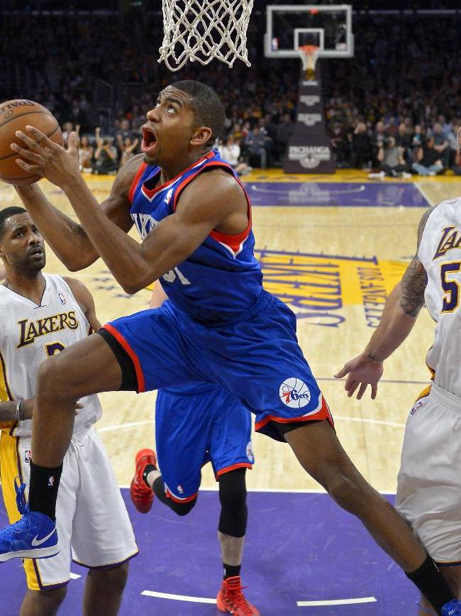 Philadelphia 76ers forward Hollis Thompson, center, puts up a shot as Los Angeles Lakers center Robert Sacre (50) defends and forward Shawne Williams, left of center, and guard Jordan Farmar looks on during the first half of an NBA basketball game, Sunday, Dec. 29, 2013, in Los Angeles