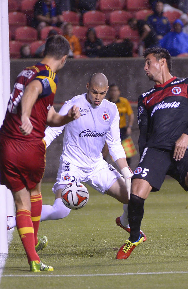 Real Salt Lake defender Chris Wingert (17) kicks the ball that is blocked by Club Tijuana goalie Gibran Lajud with defender Elio Castro. Mexican team Club Tijuana is tied 0-0 with Real Salt Lake after the first half of play, Tuesday, Aug. 12, 2014, at Rio Tinto Stadium in Sandy, Utah