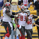 Tampa Bay Buccaneers wide receiver Vincent Jackson (83) celebrates with teammates Evan Dietrich-Smith, left, and Bobby Rainey after making a touchdown catch with only seven seconds left in the fourth quarter of the NFL football game on Sunday, Sept. 28, 2
