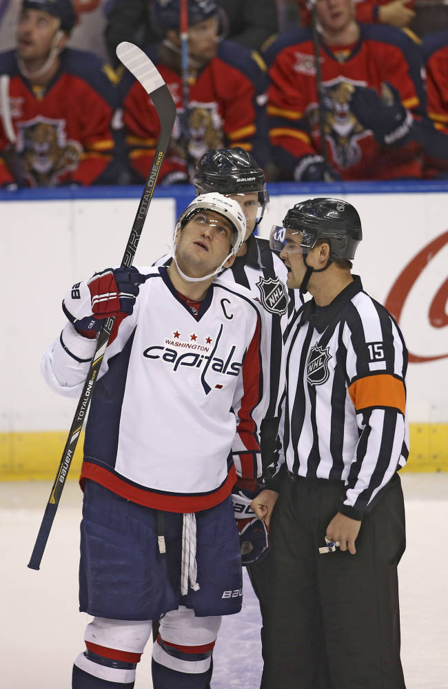 RETRANSMISSION TO CORRECT ID - Washington Captials' Alex Ovechkin protests a call by referee Jean Hebert during the first period of a NHL hockey game against the Florida Panthers in Sunrise, Fla., Friday, Dec. 13, 2013