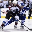 Toronto Maple Leafs' Stephane Robidas, right, picks up a hooking penalty on Colorado Avalanche's Jamie McGinn during the first period of an NHL hockey game Tuesday, Oct. 14, 2014, in Toronto The Associated Press
