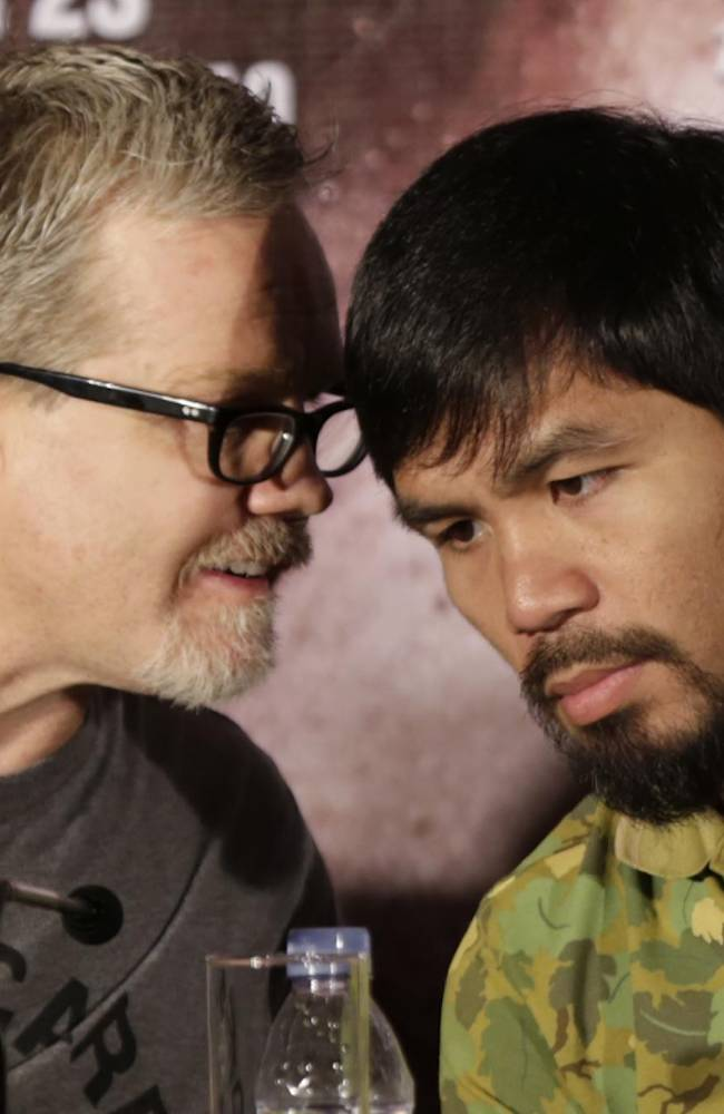 Filipino boxer and Congressman Manny Pacquiao, right, listens his trainer Freddie Roach, left, during a press conference in Shanghai, China, Wednesday, July 31, 2013. Pacquiao will fight with Brandon Rios of the United States in a welterweight bout at Venetian Macao in Nov. 24 in Macau