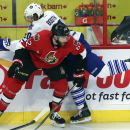 Ottawa Senators defenceman Eric Gryba (62) checks Toronto Maple Leaf forward David Booth (20) into the boards during the first period of an NHL preseason hockey game in Ottawa, Ontario, on Wednesday, Sept. 24, 2014. The Associated Press