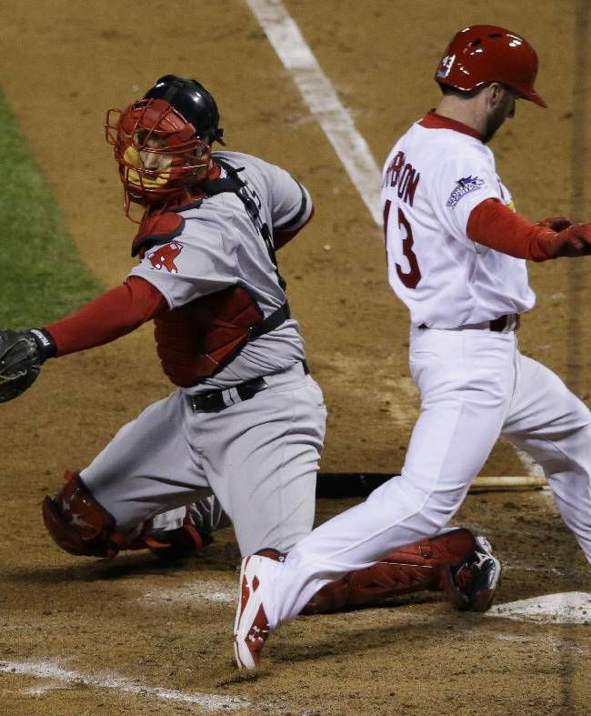 St. Louis Cardinals right fielder Shane Robinson scores past Boston Red Sox catcher David Ross on an RBI single by Matt Carpenter during the seventh inning of Game 4 of baseball's World Series Sunday, Oct. 27, 2013, in St. Louis