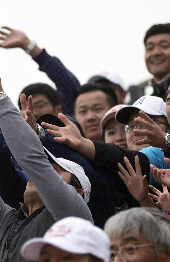 Fans fight for golf balls tossed by players after they finished the 18th hole during the final round of the Reignwood LPGA Classic golf tournament at Pine Valley Golf Club on the outskirts of Beijing, China, Sunday, Oct. 6, 2013