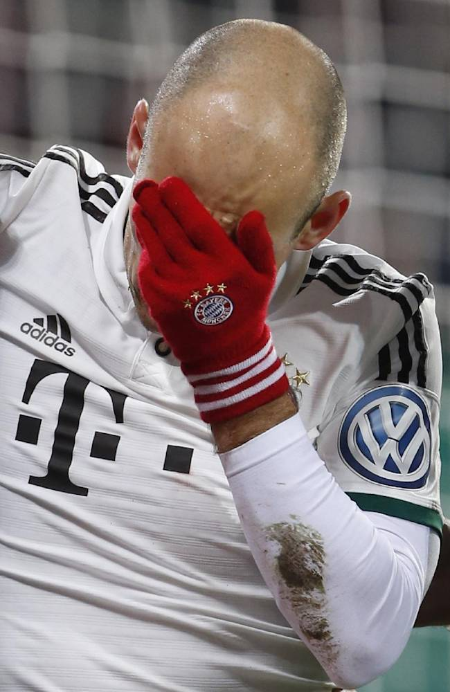 Bayern's Arjen Robben of the Netherlands covers his face after a collision with goalkeeper Marwin Hitz of Switzerland during the German soccer cup third round match between FC Augsburg and FC Bayern Munich in Augsburg, southern Germany, Wednesday, Dec. 4, 2013