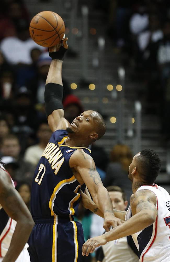 Indiana Pacers power forward David West (21) reachs for a pass as Atlanta Hawks power forward Mike Scott (32) defends in the second half of an NBA basketball game, Tuesday, Feb. 4, 2014, in Atlanta. Indiana won 89-85