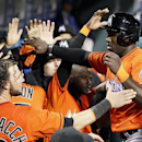 Miami Marlins' Marcell Ozuna, right, high-fives teammates after he scored on Giancarlo Stanton's two-run homer during the seventh inning of a baseball game against the , Saturday, April 12, 2014, in Philadelphia. The Phillies won 5-4 in the tenth inning T