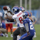 New York Giants' Mario Manningham, left, makes a catch during a NFL football camp in East Rutherford, N.J., Wednesday, July 23, 2014 The Associated Press