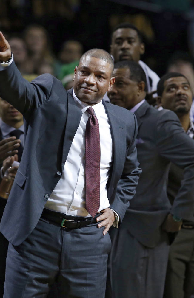Current Los Angeles Clippers head coach and former Boston Celtics head coach Doc Rivers acknowledges fans during a video tribute to him in his first time back to the TD Garden after the first quarter of an NBA basketball game in Boston, Wednesday, Dec. 11, 2013. Applauding are Clippers Chris Paul, left, and Blake Griffin, far right