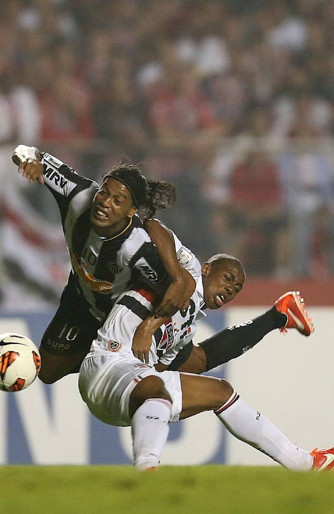 In this May 2, 2013 file photo, Ronaldinho of Brazil's Atletico Mineiro, left, and Wellington of Brazil's Sao Paulo FC battle for control of the ball during a Copa Libertadores soccer match in Sao Paulo, Brazil
