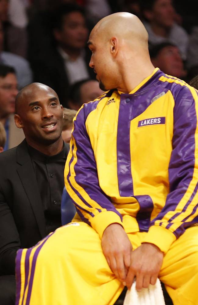 Los Angeles Lakers' Kobe Bryant, left, talks with Lakers' center Robert Sacre, right, as he sits behind the team's bench against the Los Angeles Clippers during the first half of an NBA basketball game in Los Angeles, Tuesday, Oct. 29, 2013