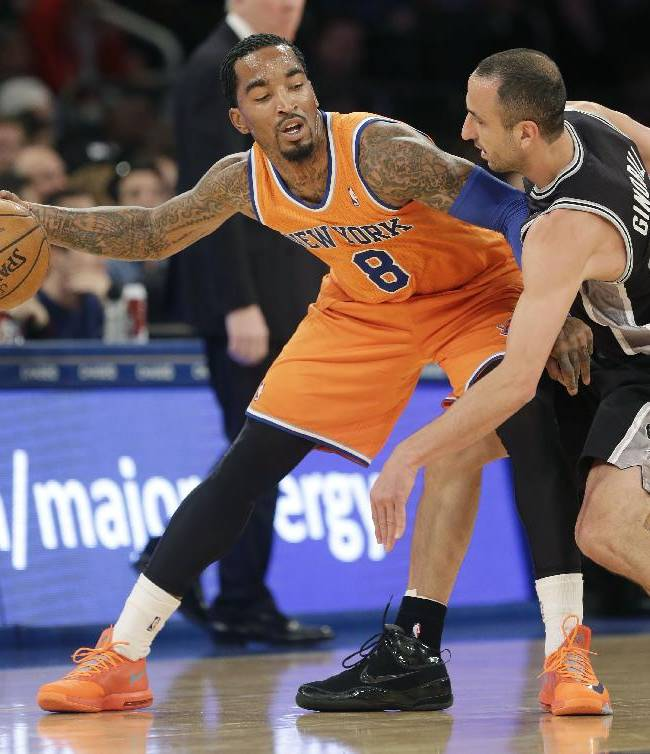 New York Knicks' J.R. Smith, left, keeps the ball from San Antonio Spurs' Manu Ginobili during the first half of the NBA basketball game at Madison Square Garden Sunday, Nov. 10, 2013 in New York
