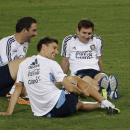 From left, Argentina's Gonzalo Higuain, Federico Fernandez and Lionel Messi sit on the pitch during a training session at the Rome Olympic stadium, Monday, Aug.12, 2013. Argentina will play Italy in a friendly match scheduled for Wednesday, Aug.14. Both teams players and staff members will be received by Pope Francis in a private audience at the Vatican the day before the match. (AP Photo/Andrew Medichini)