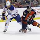 Edmonton Oilers center Matt Hendricks (23) and Florida Panthers defenseman Aaron Ekblad (5) chase the puck in the first period of an NHL hockey game, Saturday, Jan. 17, 2015, in Sunrise, Fla The Associated Press