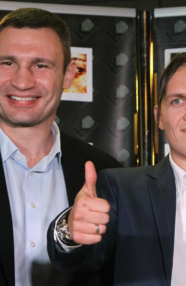 Lawmaker and chairman of the Ukrainian opposition party Udar (Punch), and WBC Heavyweight Champion boxer Vitali Klitschko, left, and Ukrainian boxer, Olympic champion Oleksandr Usyk pose for a photo during a news conference in Kiev, Ukraine, Wednesday, Sept. 25, 2013.  Oleksandr Usyk has signed a five year contract to join the professional boxing promotion company of the Klitschko brothers