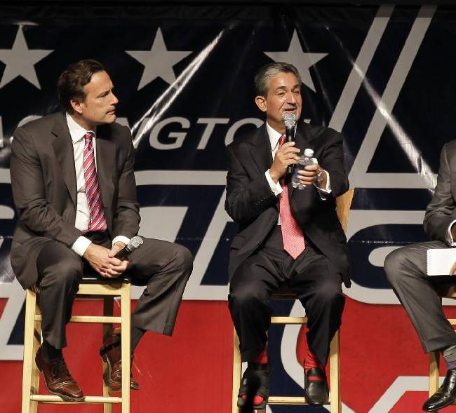Washington Capitals majority owner Ted Leonsis, center, speaks as NHL Chief Operating Officer John Collins, left,  and moderator Michael Wilbon, right, look on during the team's Capitals Convention, Saturday, Sept. 21, 2013, in Washington. Leonsis announced that the team will host the league's annual Winter Classic outdoor hockey game on New Year's Day in 2015