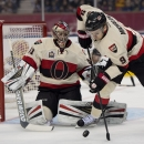 Ottawa Senators left wing Milan Michalek (9) tires to clear the puck away from Ottawa Senators goalie Craig Anderson (41) during the first period of Heritage Classic hockey game action against the Vancouver Canucks at BC Place in Vancouver, B.C., Sunday,
