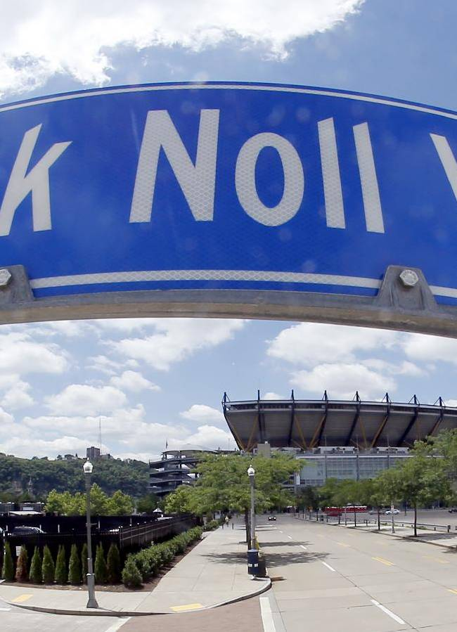 In this photo made with a fisheye lens, Heinz Field, where the Pittsburgh Steelers now play their NFL football games, is visible on Saturday, June 14, 2014, under the sign marking the street named Chuck Noll Way where Three Rivers Stadium stood when Noll coached the Steelers for 23 seasons in Pittsburgh. Noll, the Hall of Fame coach who won a record four Super Bowl titles with the Pittsburgh Steelers, died Friday, June 13, at his home. He was 82. The Allegheny County Medical Examiner said Noll died of natural causes