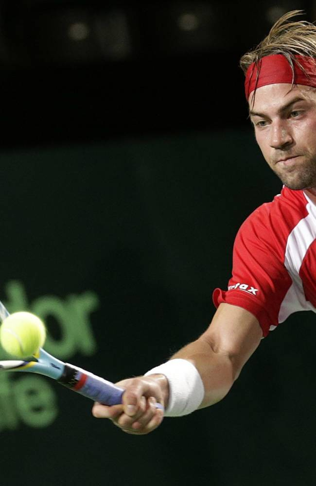 Michael Lammer of Switzerland returns a ball to Roberto Quiroz of Ecuador, during the third single match of the Davis Cup World Group Play-off round between Switzerland and Ecuador, in Neuchatel, Switzerland, Sunday, Sept.  15, 2013