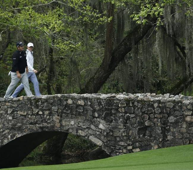 Patrick Reed, left, walks across the Byron Nelson Bridge with Rory McIlroy, of Northern Ireland, during a practice round for the Masters golf tournament Tuesday, April 8, 2014, in Augusta, Ga
