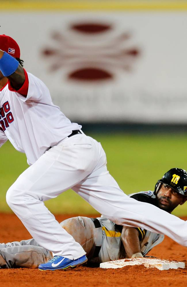Venezuela's infielder Alberto Callaspo looks up from second base after he is tagged out by Puerto Rico's infielder Iving Falu, left, in their Caribbean Series baseball game in Porlamar, Venezuela, Wednesday, Feb. 5, 2014