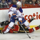 Edmonton Oilers' Benoit Pouliot (67), steals the puck from Calgary Flames' David Wolf, from Germany, during second period NHL hockey action in Calgary, Alberta, Saturday, Jan. 31, 2015 The Associated Press