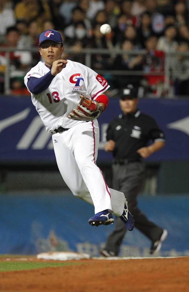 Taiwan's Lee Tu-hsuan throws to first base in the 6th inning during an exhibition game against Japan at the Xinzhuang baseball stadium in New Taipei City, Taiwan, Friday, Nov. 8, 2013. Japan beat Taiwan 4-2