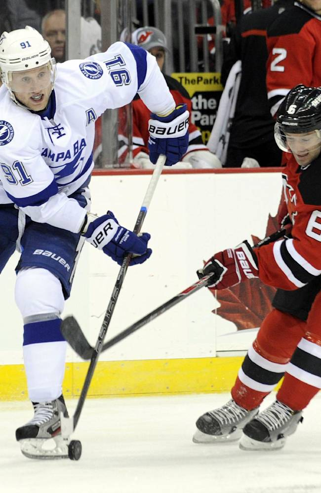 Tampa Bay Lightning center Steven Stamkos, left, controls the puck as he is checked by New Jersey Devils' Andy Greene during the first period of an NHL hockey game Tuesday, Oct. 29, 2013, in Newark, N.J