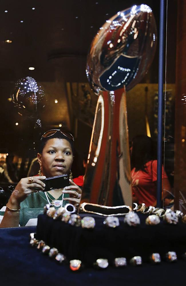 Football fan Cindy Lawrence of Hempstead, N.Y. prepares to take a photo of the Lombardi Trophy while visiting various fan zones inside Radio City Music Hall during the fourth round of the 2014 NFL Draft, Saturday, May 10, 2014, in New York