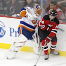 New Jersey Devils center Adam Henrique, right, makes a pass to center Scott Gomez as New York Islanders goalie Jaroslav Halak, left, of Slovakia, leaves his net during the third period of an NHL hockey game, Friday, Jan. 9, 2015, in Newark, N.J. Gomez sco