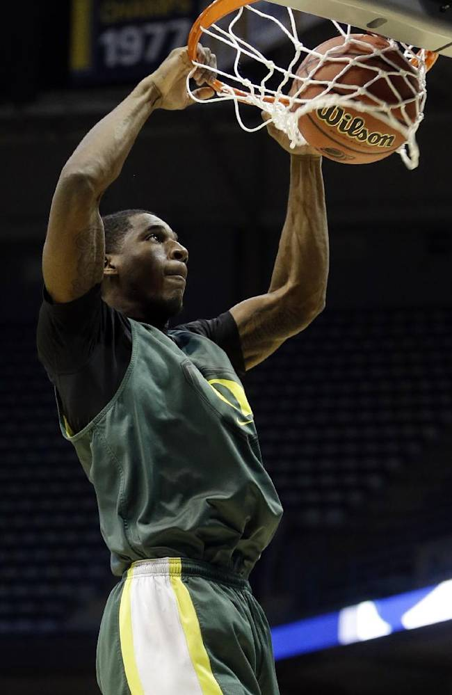Oregon guard Damyean Dotson dunks during a practice session for their NCAA college basketball tournament game Wednesday, March 19, 2014, in Milwaukee. Oregon plays BYU on Thursday, March 20, 2014