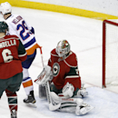 A shot by New York Islanders defenseman Nick Leddy gets past Minnesota Wild goalie Niklas Backstrom, right, of Finland, Wild defenseman Marco Scandella (6) and Islanders center Brock Nelson (29) for a goal during the first period of an NHL hockey game in