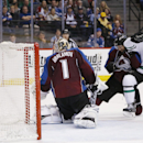 Dallas Stars center Cody Eakin, right, is checked by Colorado Avalanche defenseman Brad Stuart, center, as Eakin's shot bounces past Avalanche goalie Semyon Varlamov, of Russia, to the boards in the second period of an NHL hockey game Saturday, Jan. 10, 2