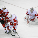 New Jersey Devils' Stephen Gionta (11) tips the puck past Detroit Red Wings goaltender Jimmy Howard for a goal as he is checked by Red Wings' Danny DeKeyser (65) and Justin Abdelkader (8) during the third period of an NHL hockey game Tuesday, March 4, 201