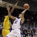 Northwestern forward Jared Swopshire, right, drives to the basket as Minnesota guard Austin Hollins defends during the second half of an NCAA college basketball game in Evanston, Ill., Wednesday, Jan. 23, 2013. Northwestern won 55-48. (AP Photo/Nam Y. Huh)