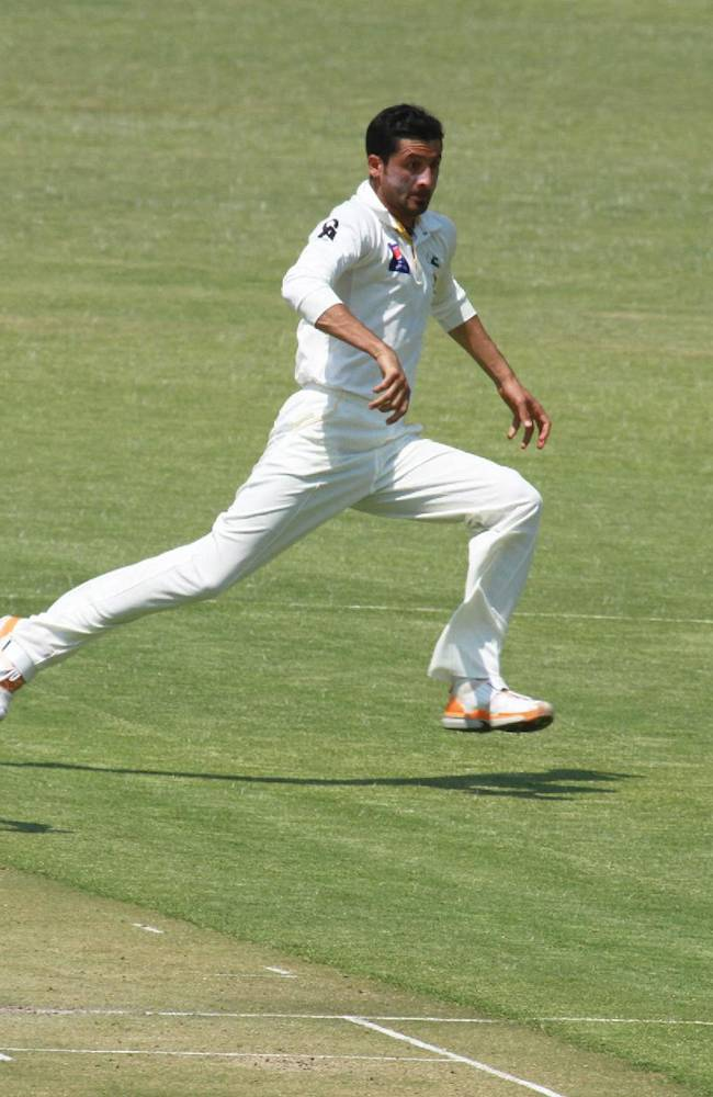 Pakistan bowler Junaid Khan , right, runs after the ball on the first day of the  last  test match   against Zimbabwe at Harare Sports Club  in Harare, Tuesday, Sept, 10, 2013. Pakistan is in Zimbabwe  to play Test matches against the hosts