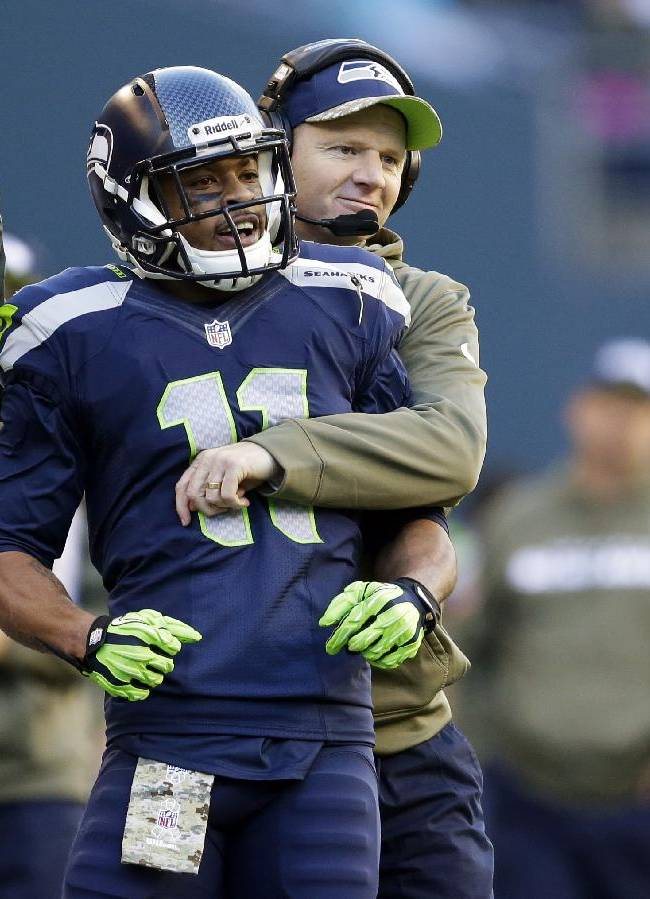 Seattle Seahawks' wide receiver Percy Harvin (11) is hugged on the sideline by Seattle Seahawks offensive coordinator Darrell Bevell during an NFL football game against the Minnesota Vikings, Sunday, Nov. 17, 2013, in Seattle. The game was Harvin's first back on the field following hip surgery earlier in the year and his first against the Vikings since he was traded to the Seahawks. The Seahawks won 41-20