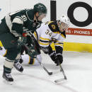 Minnesota Wild defenseman Ryan Suter (20) and Boston Bruins center Carl Soderberg (34), of Sweden, chase the puck during the first period of an NHL hockey game in St. Paul, Minn., Wednesday, Dec. 17, 2014. (AP Photo/Ann Heisenfelt)