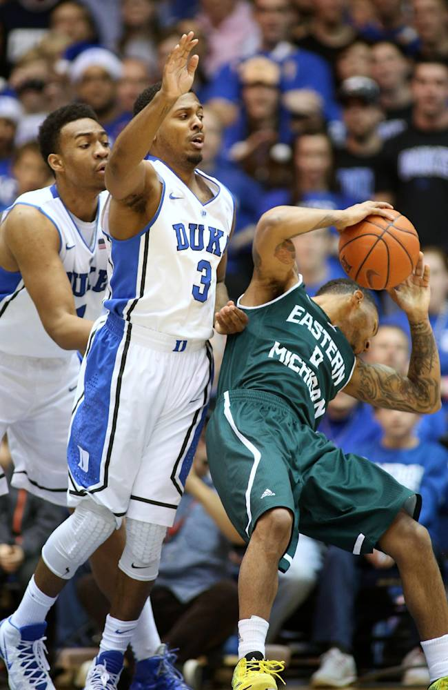 Eastern Michigan's Raven Lee, right, loses his balance while being guarded by Duke's Jabari Parker, left, and Tyler Thornton, center, during the first half of an NCAA college basketball game in Durham, N.C., Saturday, Dec. 28, 2013